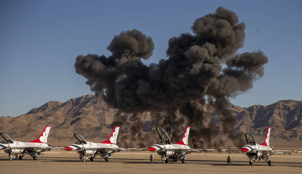 A mock explosion fills the sky with black smoke beyond the U.S. Air Force Thunderbirds during t ...