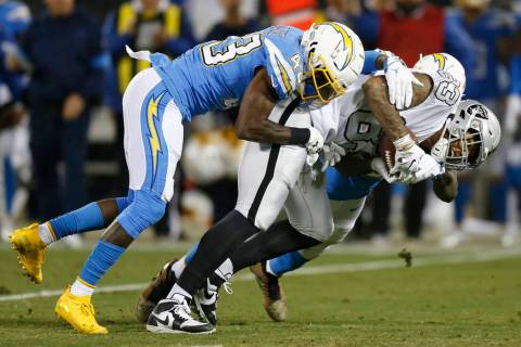 Oakland Raiders tight end Darren Waller, right, is tackled by Los Angeles Chargers cornerback M ...