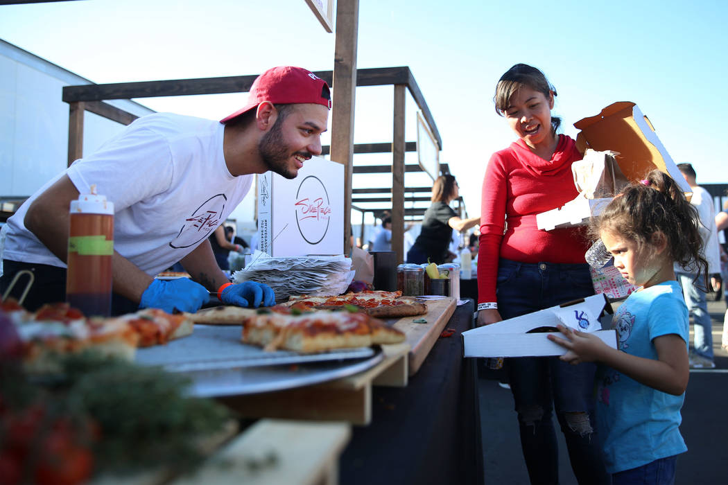 Enzo Esposito, left, executive pizza chef for Side Piece Pizza, asks Wenda Swords and her daugh ...