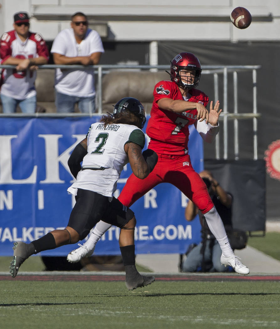 UNLV Rebels quarterback Kenyon Oblad (7) makes a throw on the run over Hawaii Warriors lineback ...