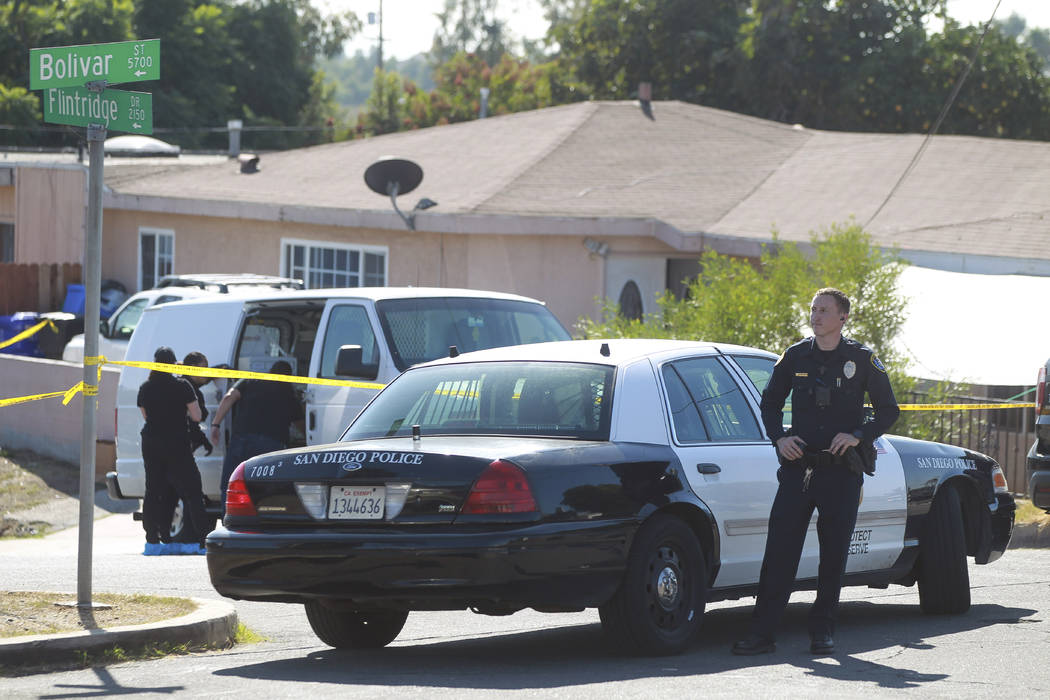 A San Diego Police officer stands in front of a home where two adults and three children died f ...