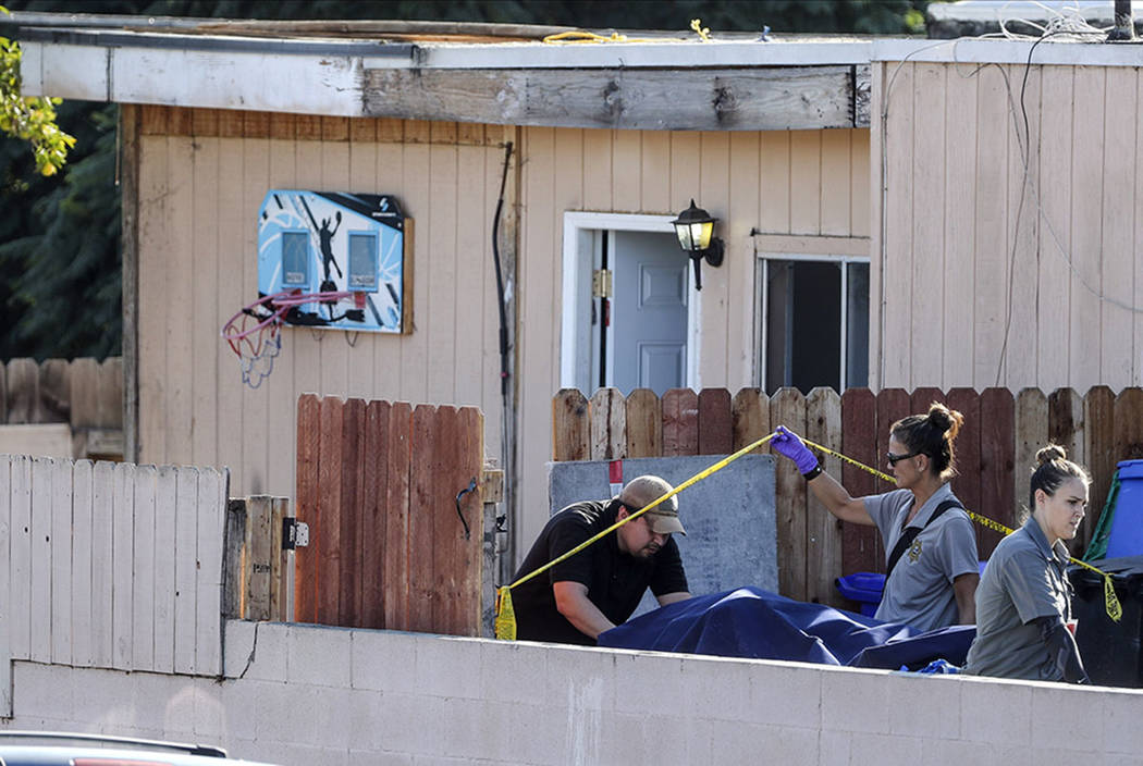 A body is carried out on a gurney at the home where two adults and three children died from gun ...