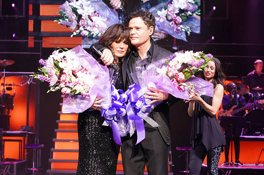 Flamingo Las Vegas President Eileen Moore presents Donny and Marie Osmond with flowers onstage ...