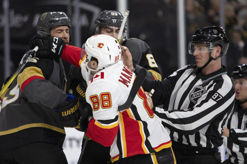 Golden Knights defenseman Deryk Engelland (5) takes a punch from Calgary Flames left wing Andre ...