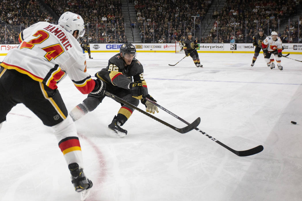 Golden Knights left wing Tomas Nosek (92) goes for the puck against Calgary Flames defenseman T ...