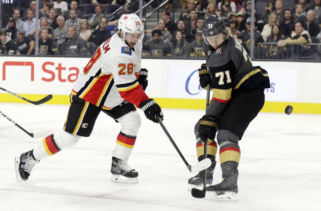 Vegas Golden Knights center William Karlsson (71) defends as Calgary Flames center Elias Lindho ...