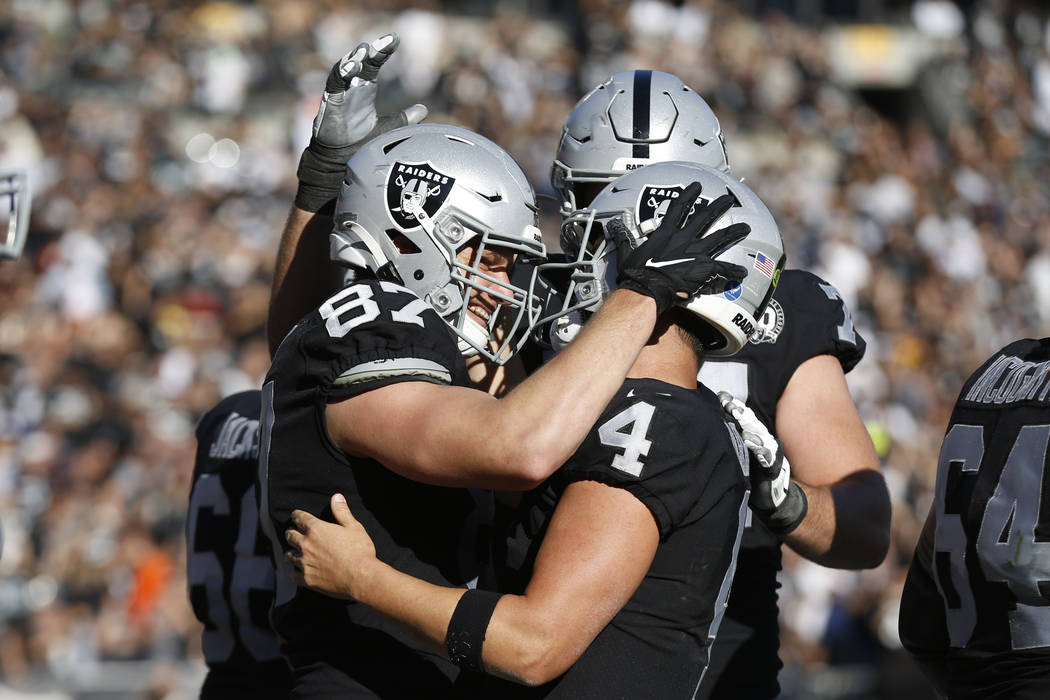 Oakland Raiders tight end Foster Moreau (87) is greeted by quarterback Derek Carr (4) after sco ...