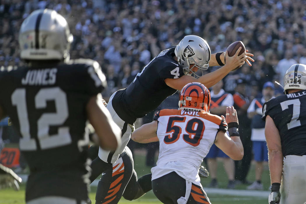 Oakland Raiders quarterback Derek Carr (4) leaps with the ball over the goal line to score a to ...