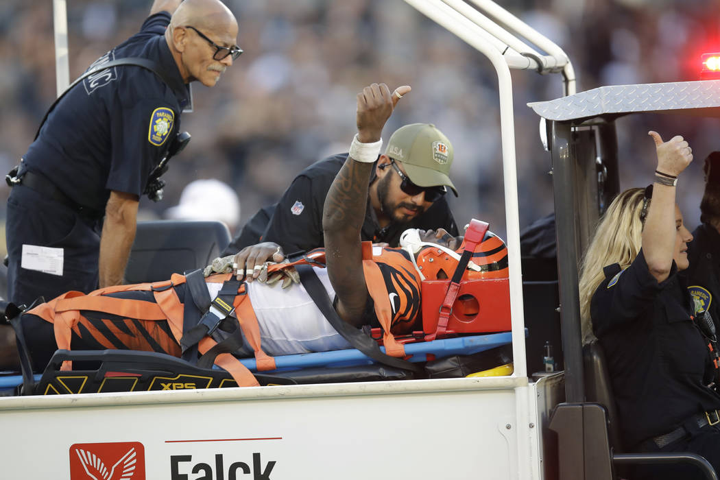 Cincinnati Bengals wide receiver Auden Tate flashes a thumbs up while being carried off the fie ...