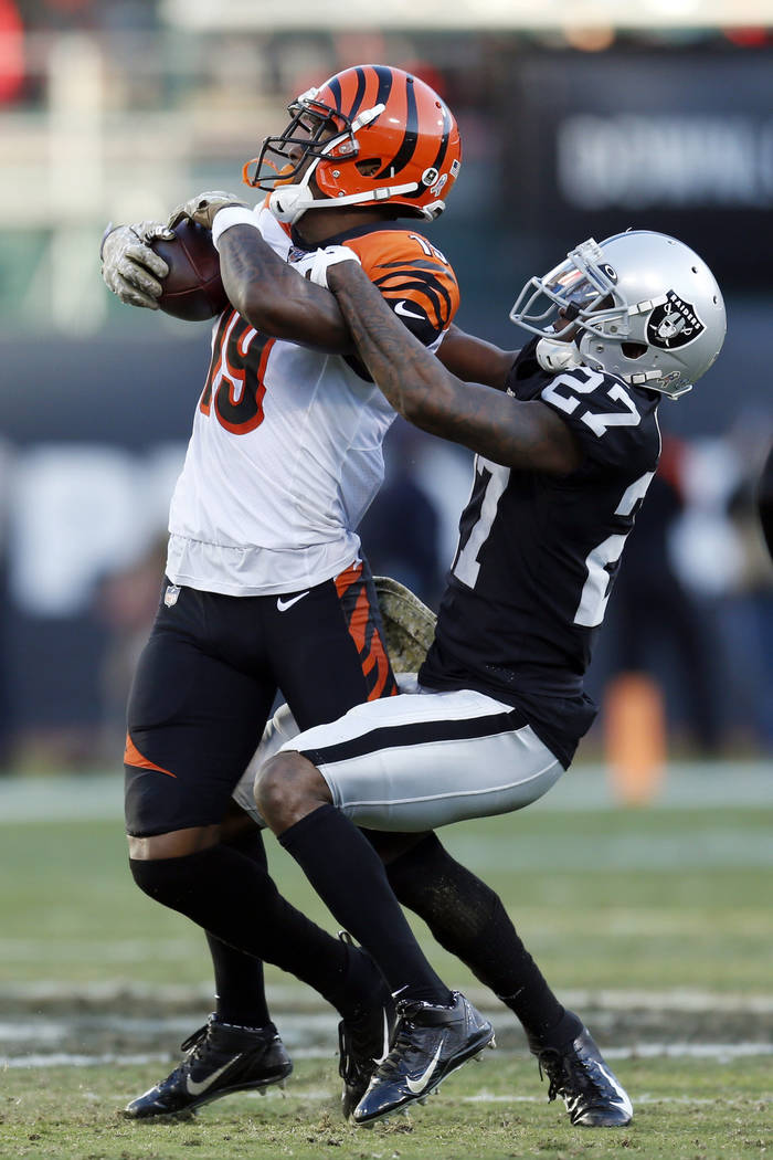 Cincinnati Bengals wide receiver Auden Tate is stopped with the ball by Oakland Raiders cornerb ...