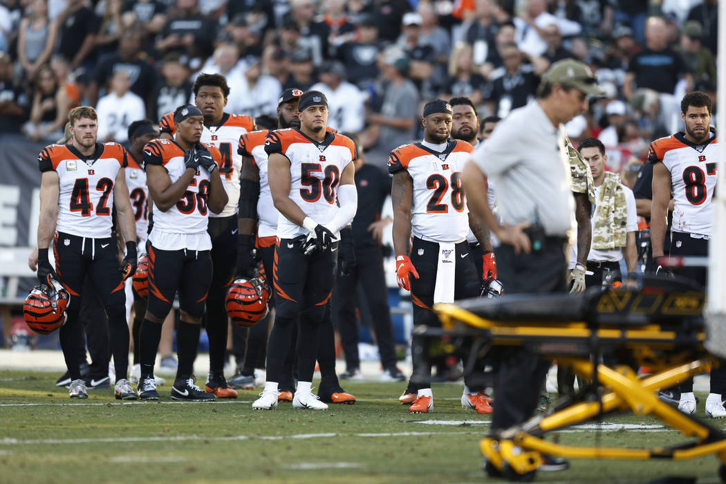 The Cincinnati Bengals look on as Bengals wide receiver Auden Tate is carried off the field aft ...