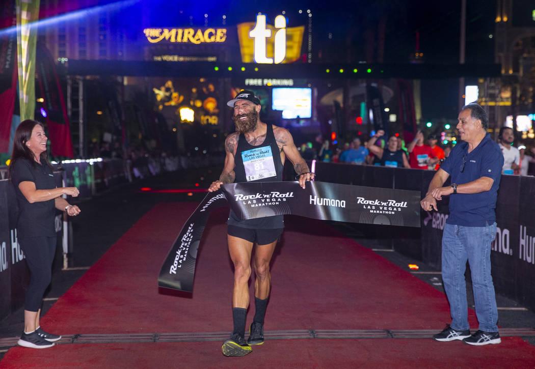 Men's marathon winner Tommy Puzey crosses the finish line during the Las Vegas Rock 'n' Roll Ma ...