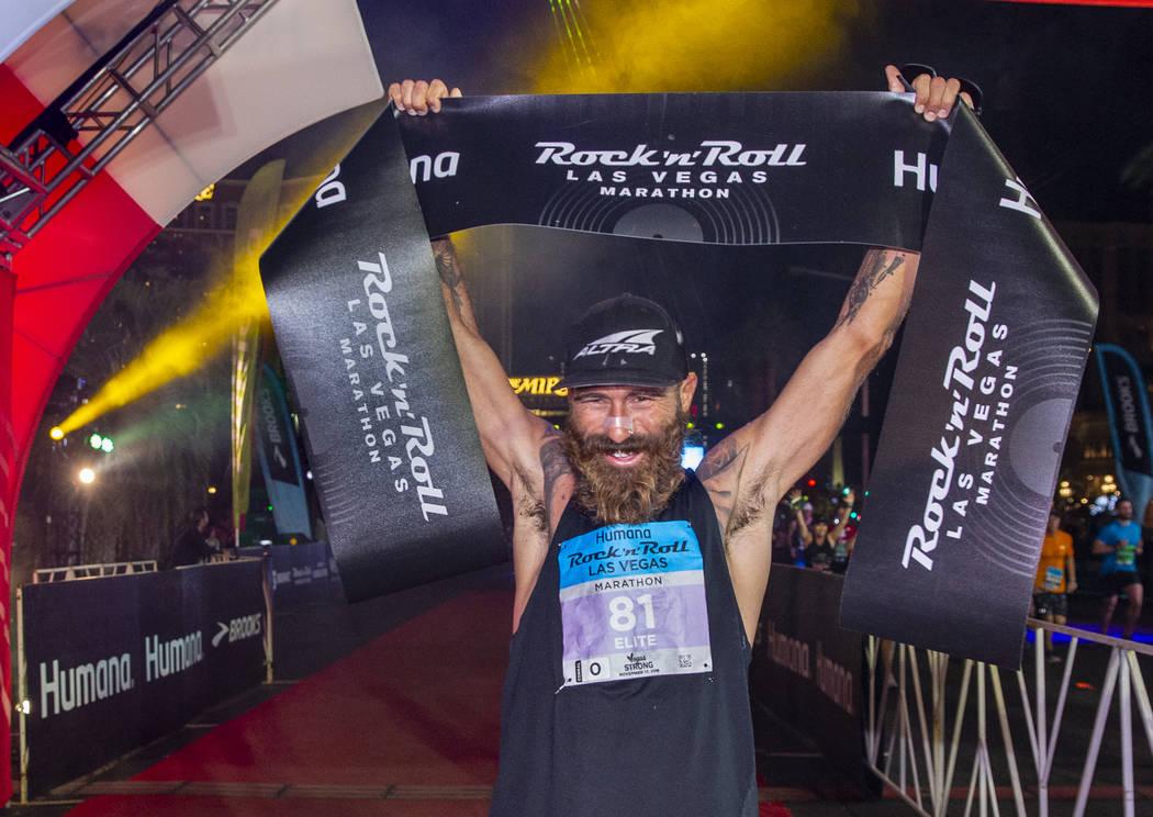 Men's marathon winner Tommy Puzey celebrates at the finish line during the Las Vegas Rock 'n' R ...