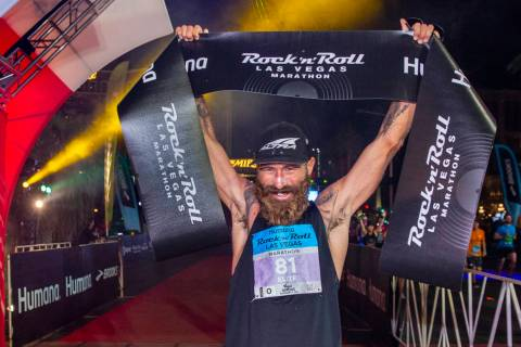 Men's marathon winner Tommy Puzey celebrates at the finish line during the Las Vegas Rock 'n' R ...