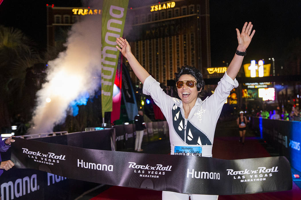Women's marathon winner Heather Bray crosses the finish line during the Las Vegas Rock 'n' Roll ...