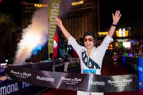Women's marathon winner Heather Bray crosses the finish line during the Las Vegas Rock 'n' Roll ...