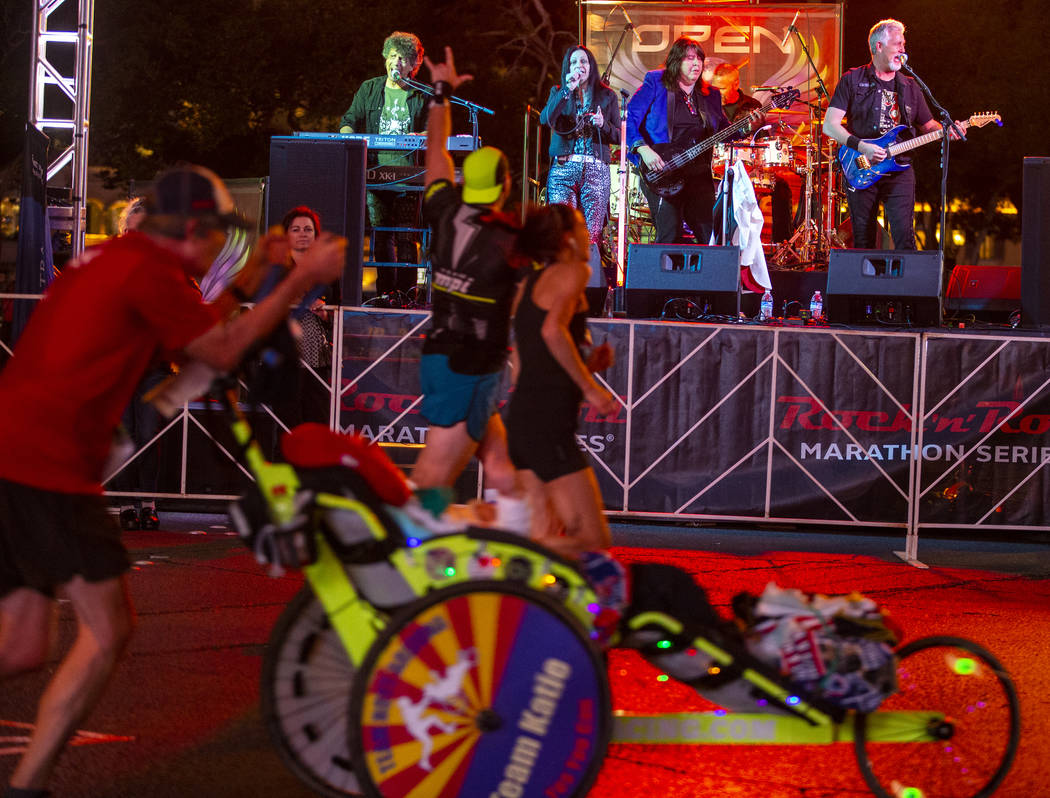Runners listen as they pass the Open Arms Journey Tribute band during the Las Vegas Rock 'n' Ro ...