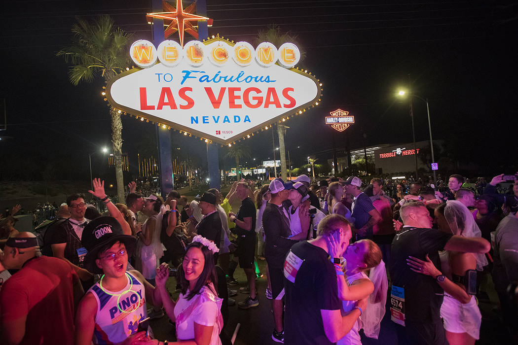 Runners are married in a mass wedding at the Las Vegas sign at the Rock ÕnÕ Roll Mara ...
