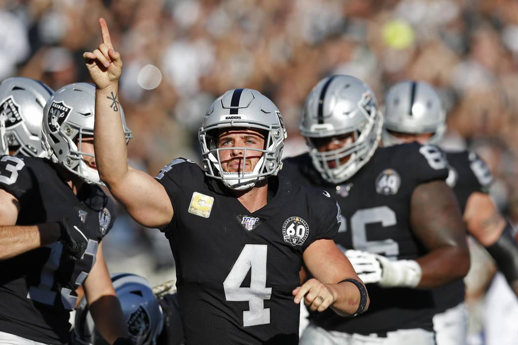 Oakland Raiders quarterback Derek Carr celebrates after scoring a touchdown during the first ha ...