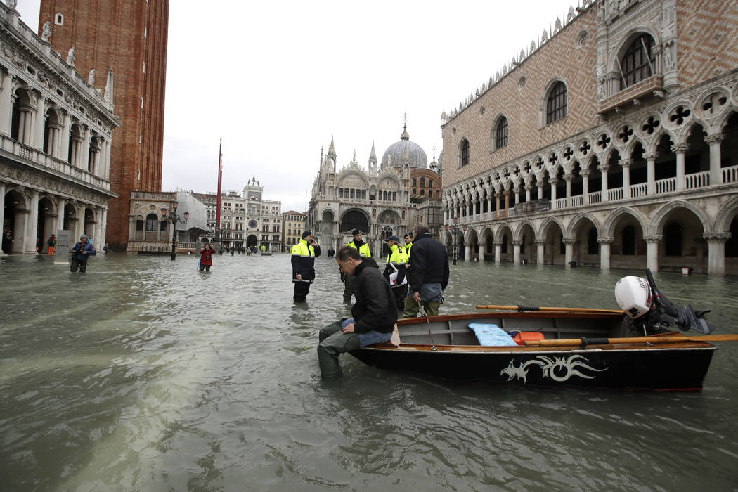 A man sits on a small boat in a flooded St.Mark square in Venice, Italy, Sunday, Nov. 17, 2019. ...