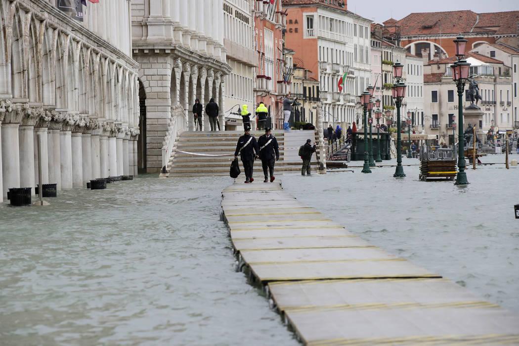 Two Carabinieri walk on a gangway in flooded Venice, Italy, Sunday, Nov. 17, 2019. Venetians ar ...
