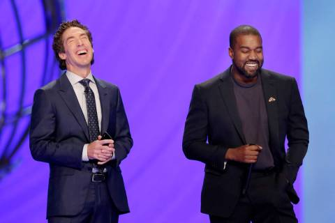 With their eyes closed for prayer, Joel Osteen, left, and Kanye West laugh as West makes a joke ...