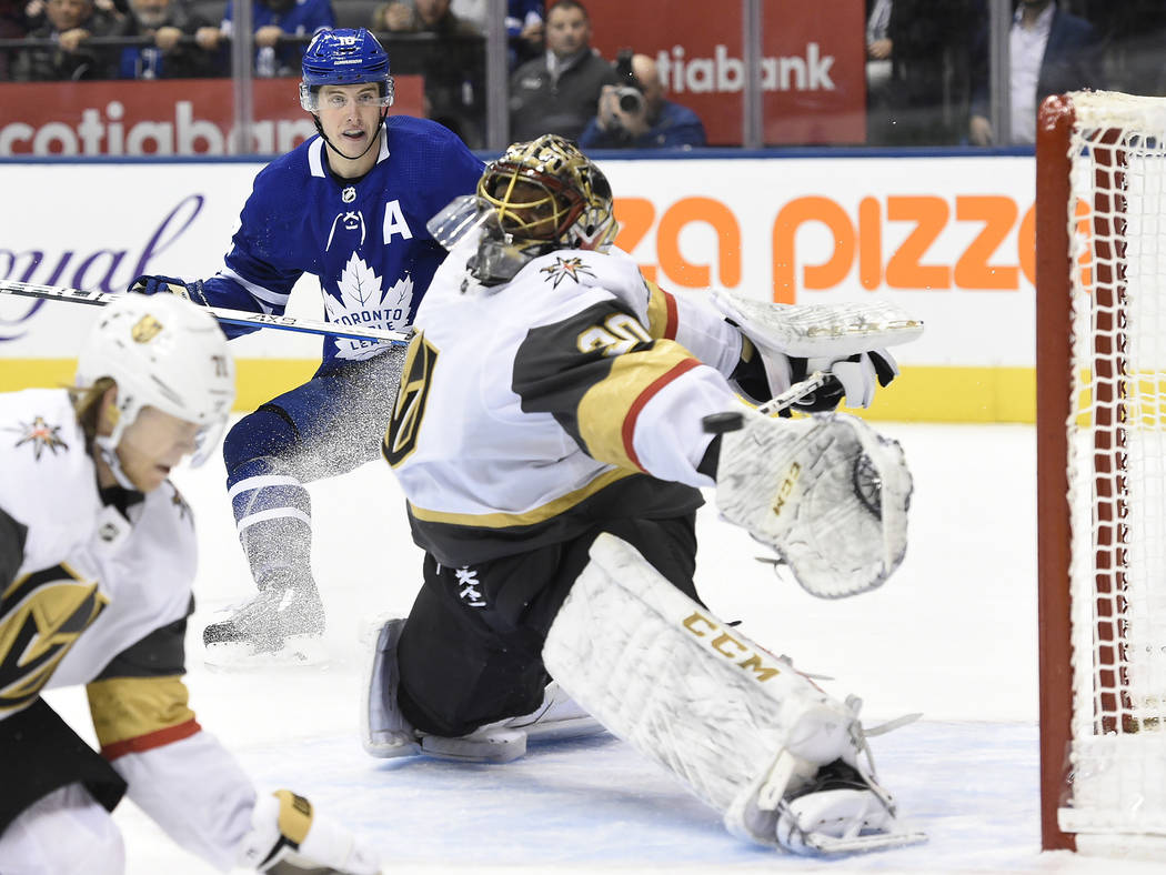 Toronto Maple Leafs center Mitchell Marner, back, watches as a goal by center John Tavares, goe ...