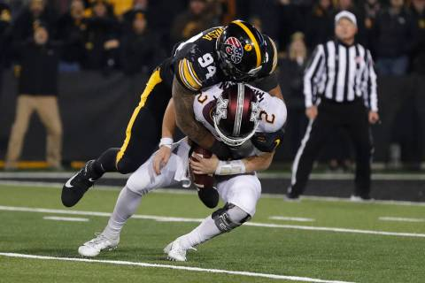 Iowa defensive end A.J. Epenesa, top, sacks Minnesota quarterback Tanner Morgan during the seco ...