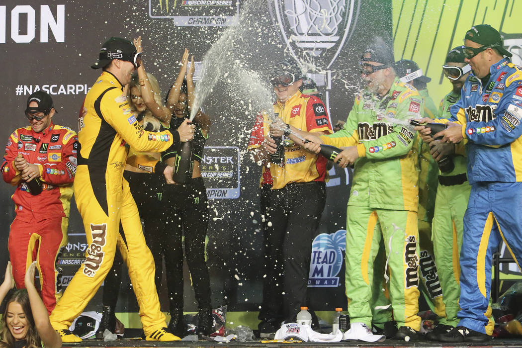 Kyle Busch, front left, celebrates with teammates in Victory Lane after winning a NASCAR Cup Se ...