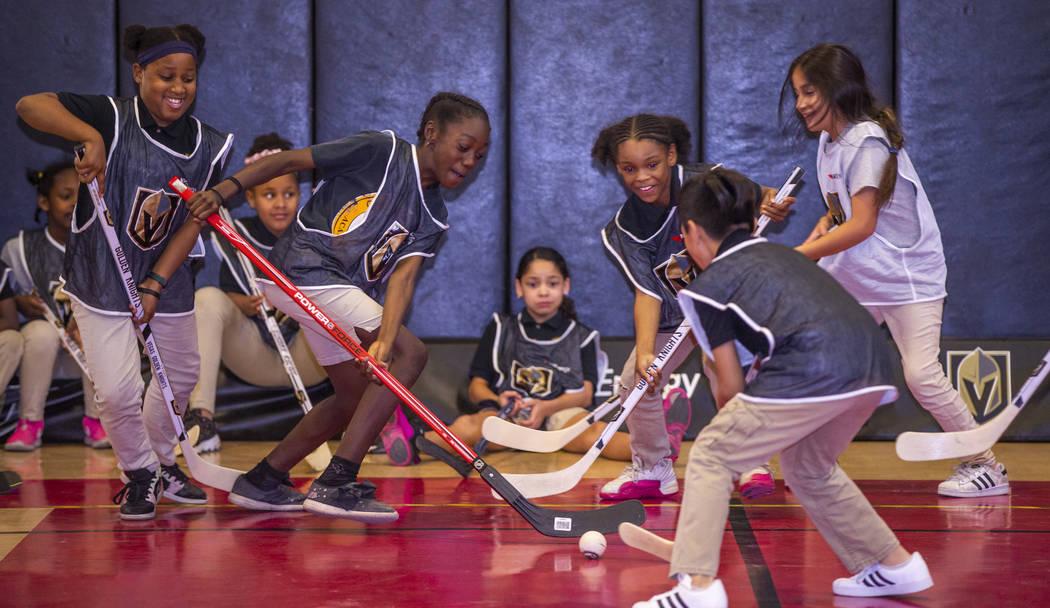 Kids at the Doc Pearson Community Center play street hockey during a street hockey clinic hoste ...