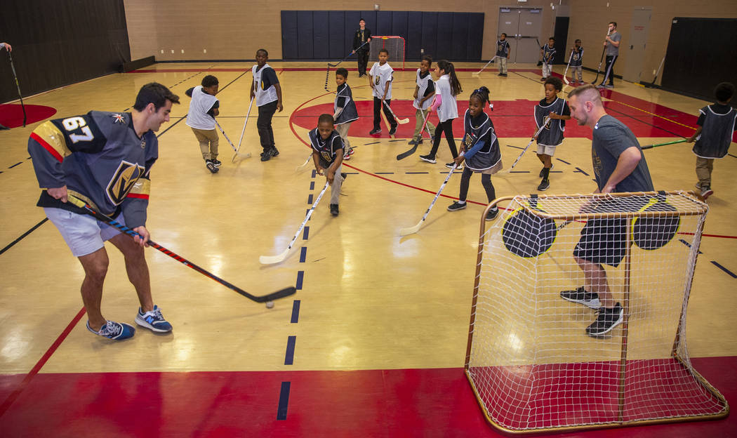 Vegas Golden Knights forward Max Pacioretty, left, plays street hockey with kids at the Doc Pea ...