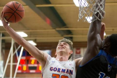 Bishop Gorman senior guard Noah Taitz (20) slices to the rim over Desert Pines junior Darnell W ...