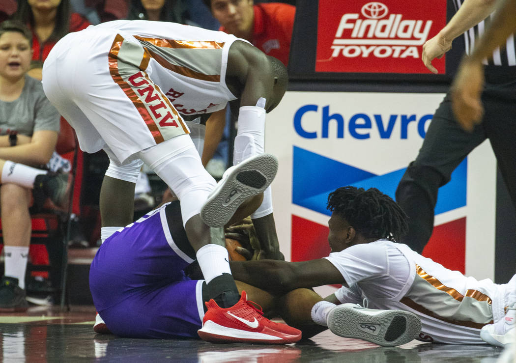UNLV Rebels forward Mbacke Diong (34, above) reaches for a loose ball with Abilene Christian Wi ...