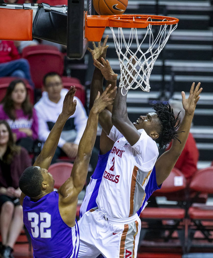 UNLV Rebels forward Donnie Tillman (2, center) gets off a shot over tight defense at the rim by ...