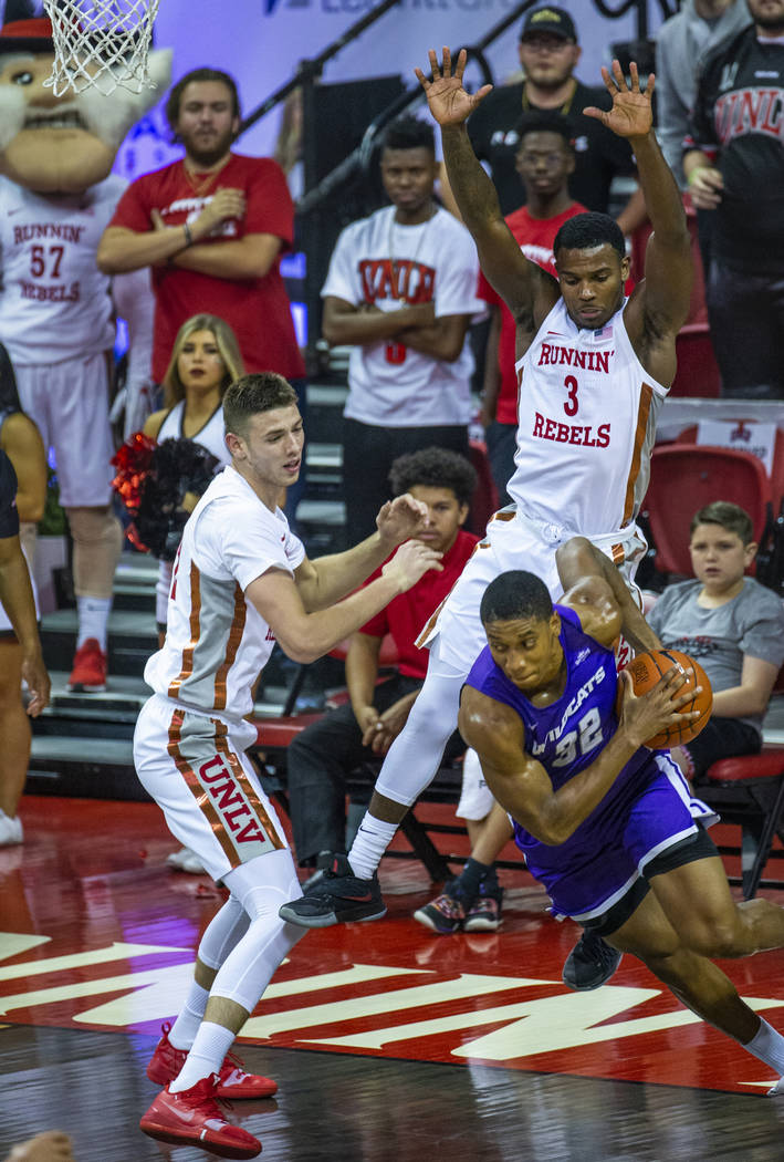 UNLV Rebels forward Vitaliy Shibel (22, left) and teammate guard Amauri Hardy (3, top right) d ...