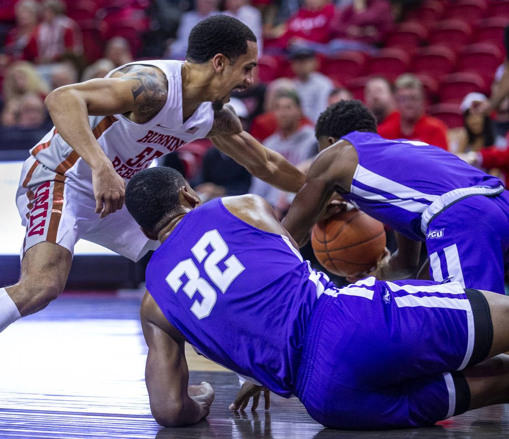 UNLV Rebels guard Elijah Mitrou-Long (55, left) gets a hand on a loose ball with a challenge fr ...