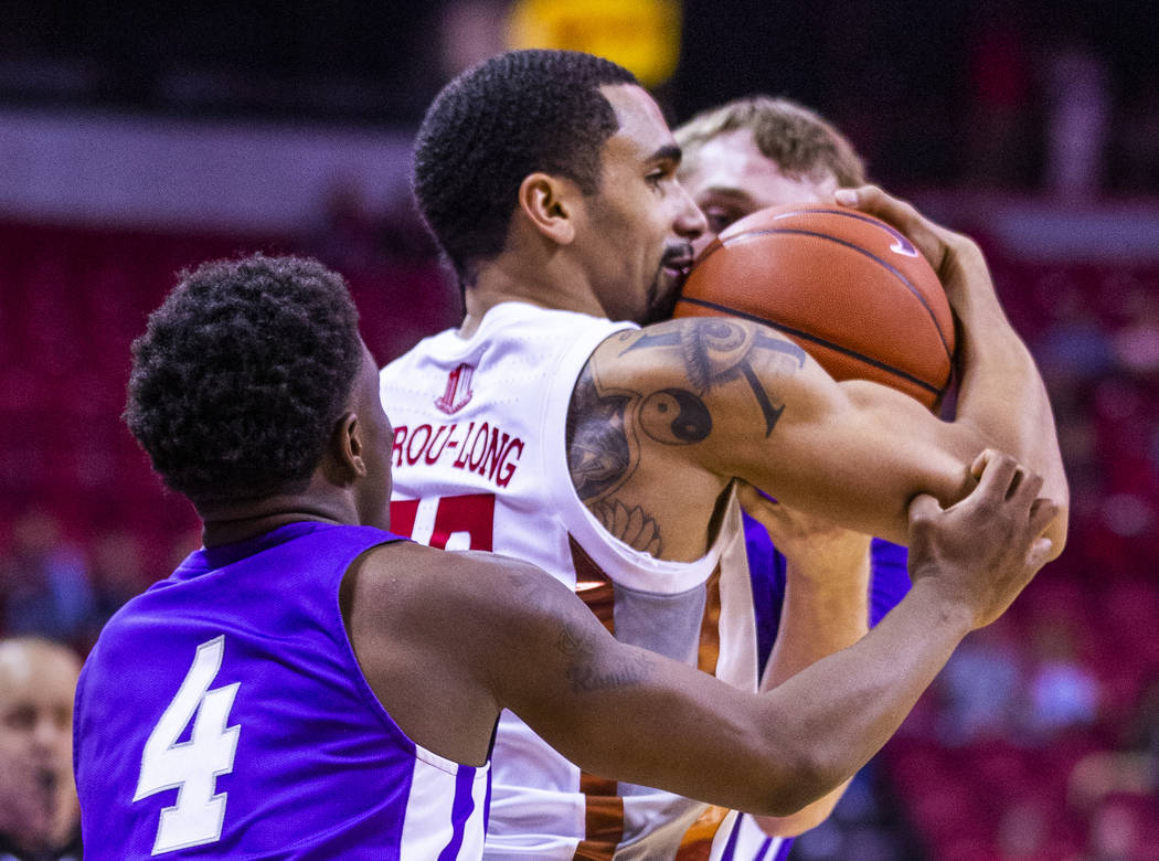 UNLV Rebels guard Elijah Mitrou-Long (55, center) secures the ball from Abilene Christian Wildc ...