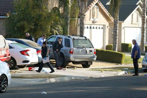 Fresno police investigators work the driveway where a shooting took place at a house party whic ...