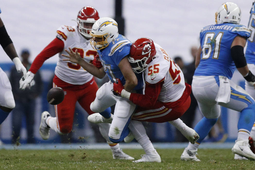 Los Angeles Chargers quarterback Philip Rivers, center, is sacked by Kansas City Chiefs defensi ...