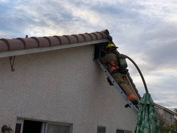 A Las Vegas Fire Department firefighter works on an attic fire in the northwest valley early Tu ...
