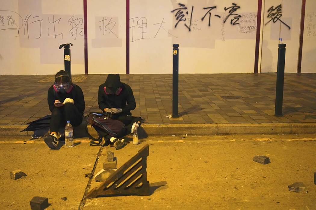 Protestors rest near a road barricaded with bricks in Hong Kong, early Tuesday, Nov. 19, 2019. ...