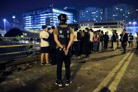 A riot policeman watches over a group of detained people on a bridge in Hong Kong, early Tuesda ...