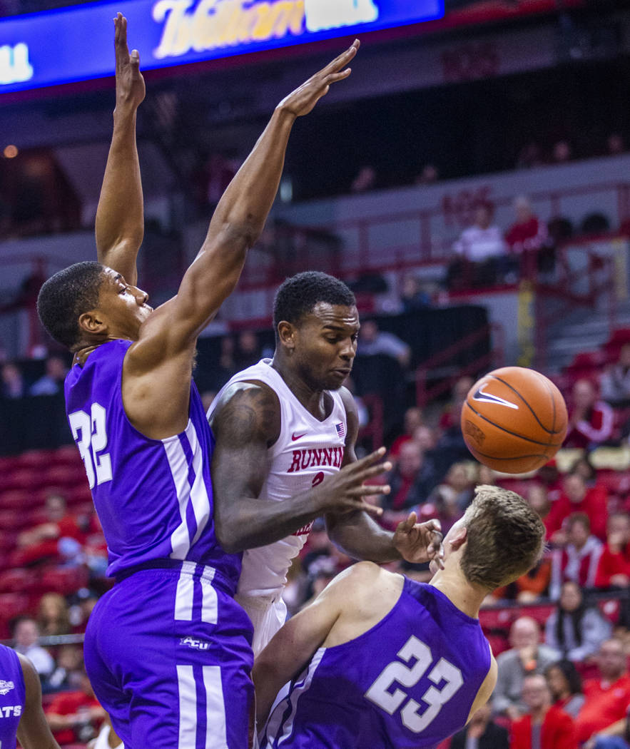 UNLV Rebels guard Amauri Hardy (3, center) is fouled on the drive by Abilene Christian Wildcats ...
