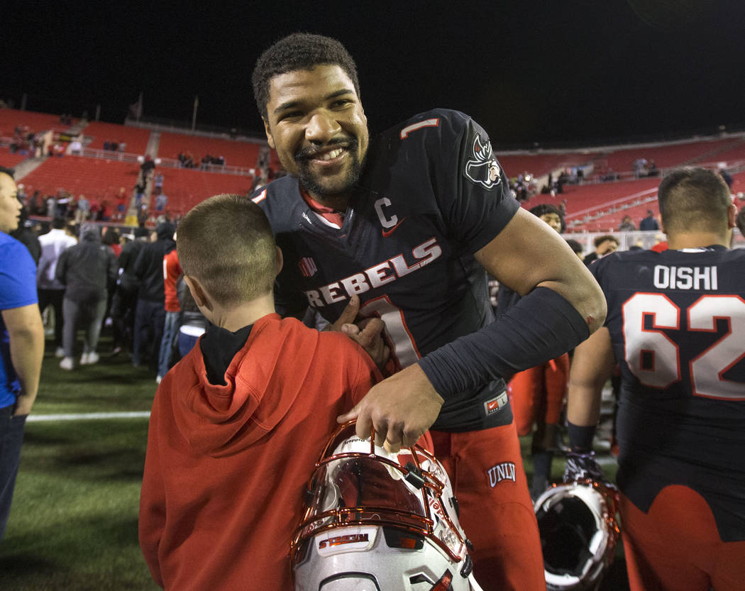 UNLV Rebels quarterback Armani Rogers (1) is greeted by fans after defeating UNR Wolf Pack 34-2 ...