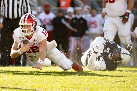 Indiana quarterback Peyton Ramsey (12) dives toward the end zone as he slips the grasp of Penn ...