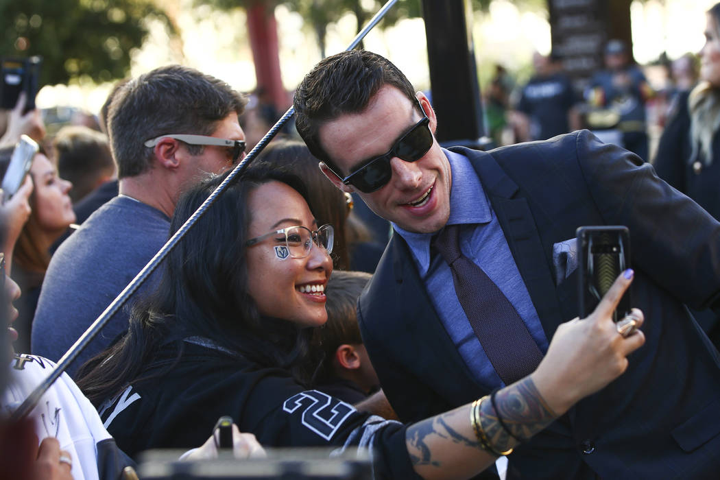 Golden Knights' Reilly Smith poses for pictures on the gold carpet after arriving for the NHL s ...