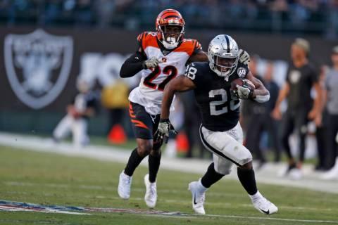 Oakland Raiders running back Josh Jacobs runs with the ball past Cincinnati Bengals cornerback ...