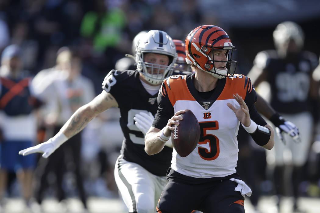 Cincinnati Bengals quarterback Ryan Finley and Oakland Raiders defensive end Maxx Crosby, left, ...