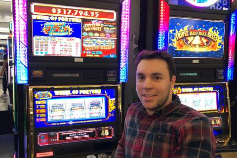Ryan C. of Columbus, Ohio, celebrates his 25-cent Wheel of Fortune Triple Red Hot 7 machine vic ...