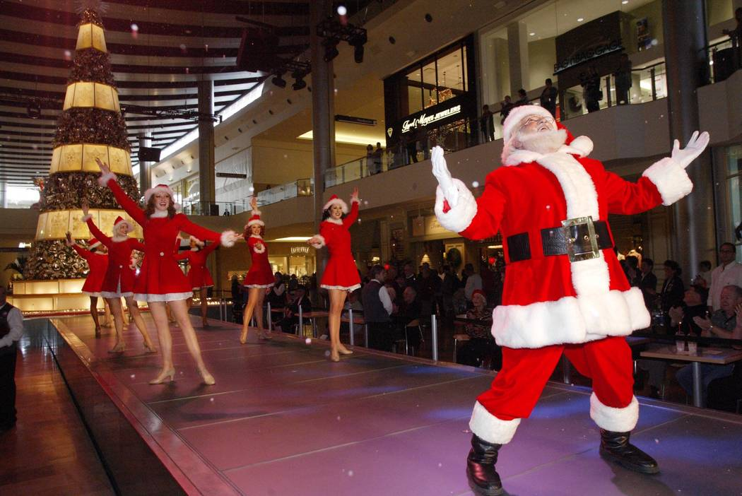 Santa Claus and the Fashion Show Girls make it snow during a performance at the Fashion Show Ma ...